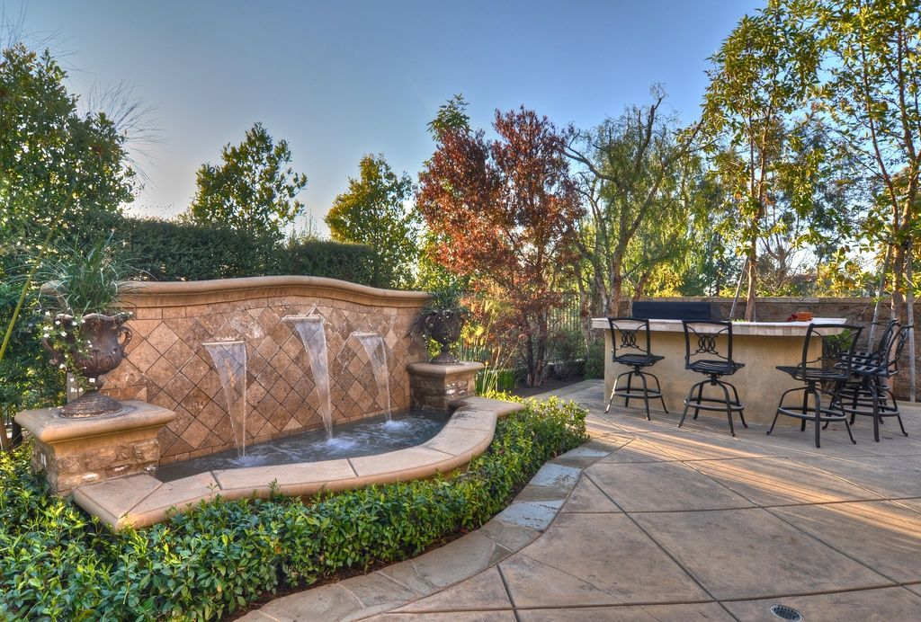 Mediterranean Patio with exterior stone floors, Outdoor metal bar stools, Fence, Fountain, Outdoor kitchen