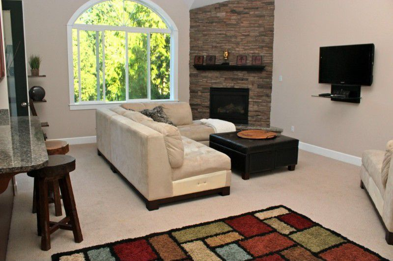 Contemporary Living Room with Carpet, High ceiling, French doors, Fireplace, Arched window, stone fireplace