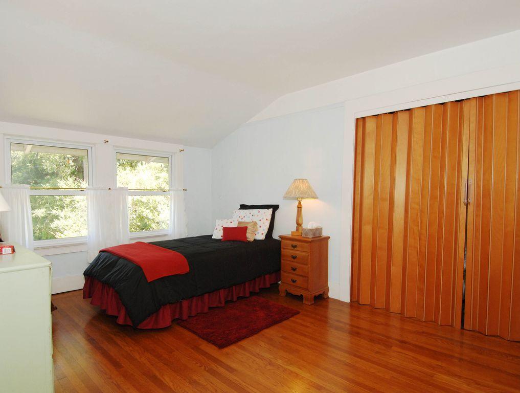 Traditional Guest Bedroom with double-hung window, Hardwood floors, Standard height, Built-in bookshelf