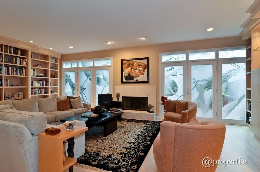 Modern Living Room with Standard height, Hardwood floors, Fireplace, can lights, Transom window, metal fireplace