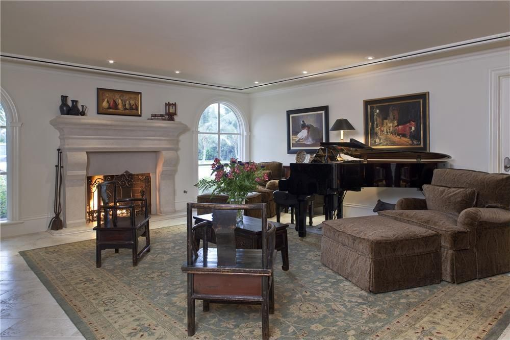 Traditional Living Room with Arched window, Standard height, Crown molding, Cement fireplace, Fireplace, stone tile floors