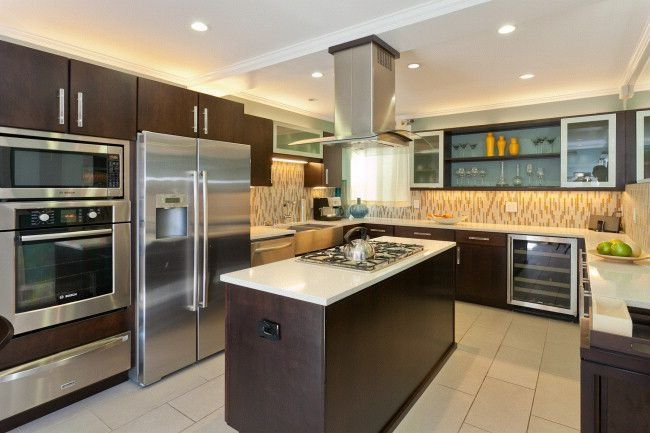 Contemporary Kitchen with Kitchen island, Wine refrigerator, wall oven, full backsplash, stone tile floors, Crown molding