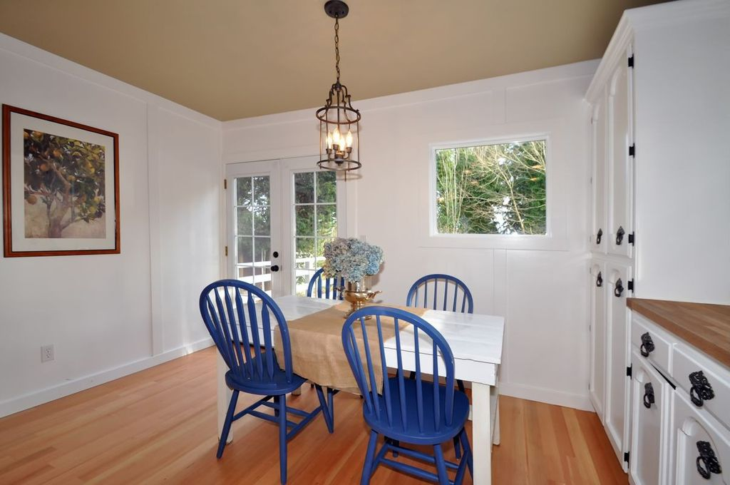 Cottage Dining Room with Crown molding, French doors, picture window, Laminate floors, Standard height, Chandelier