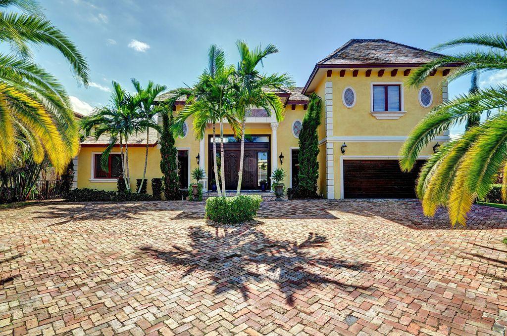 Mediterranean Exterior of Home with Fence, exterior tile floors, Transom window, Casement, exterior interlocking pavers