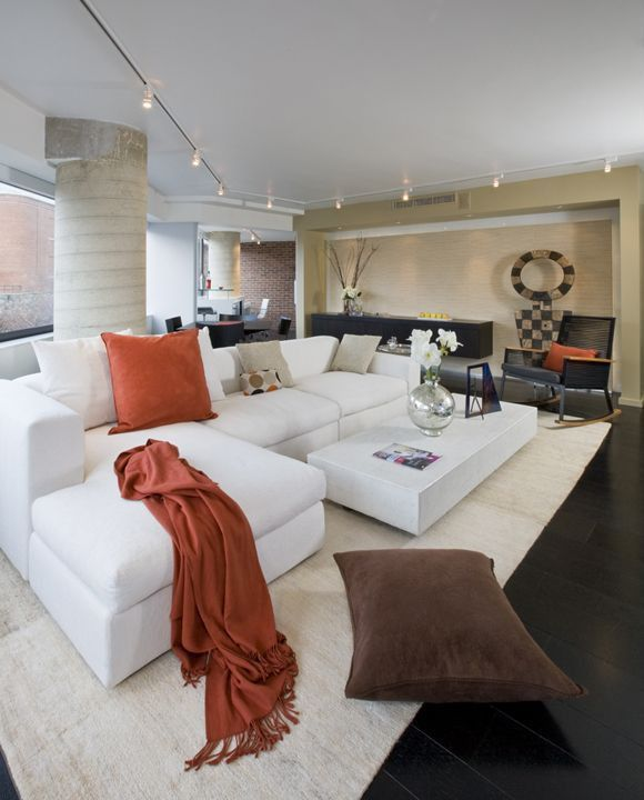 Contemporary Living Room with White sofa, Exposed brick wall, Track lighting, Hardwood floors, White area rug, Cement column