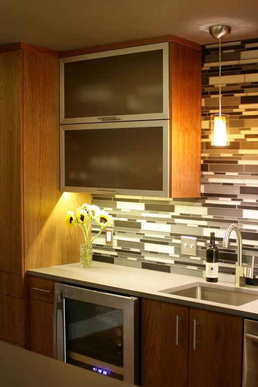 Contemporary Kitchen with Framed Partial Panel, dishwasher, Quartz counterts, Wine refrigerator, Pendant light, Glass panel