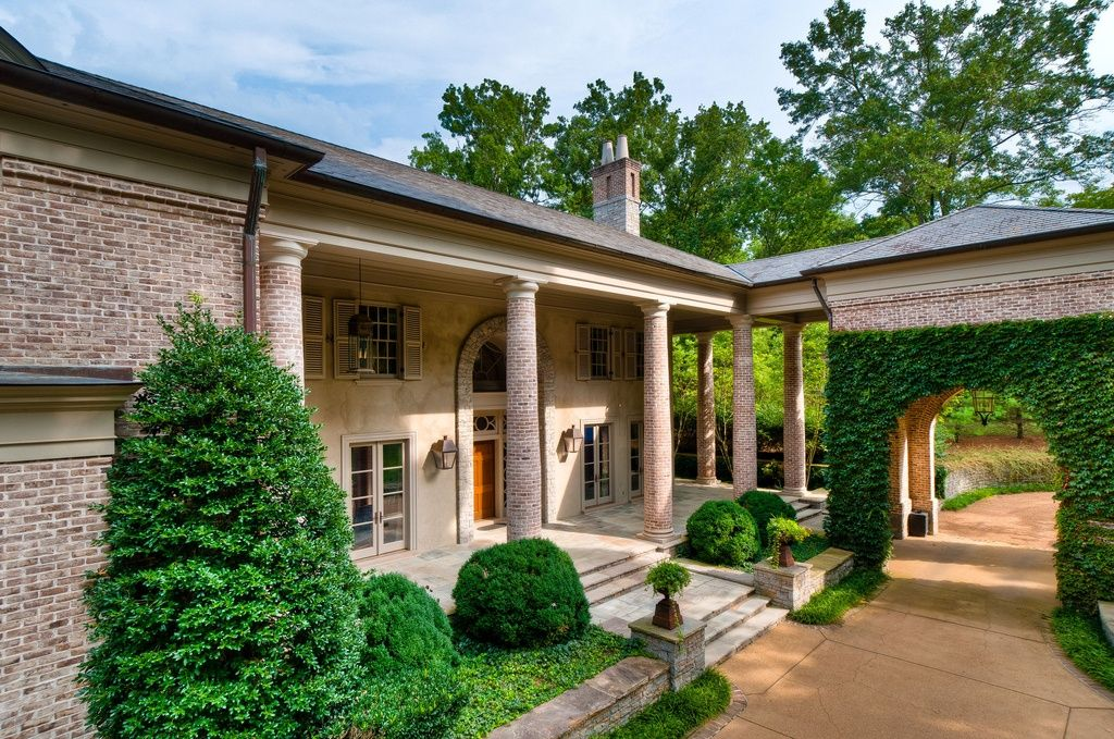 Traditional Exterior of Home with Exterior window shutters, Arched entry, Exterior brick, Pillars, Covered patio, Shutters