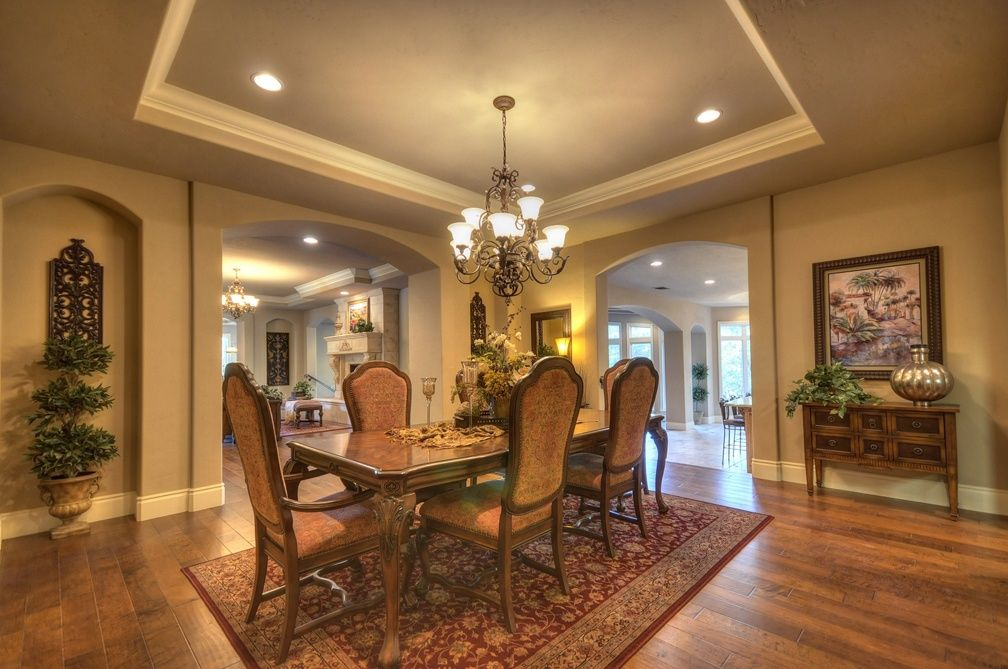 Mediterranean Dining Room with Standard height, Hardwood floors, Crown molding, can lights, Chandelier