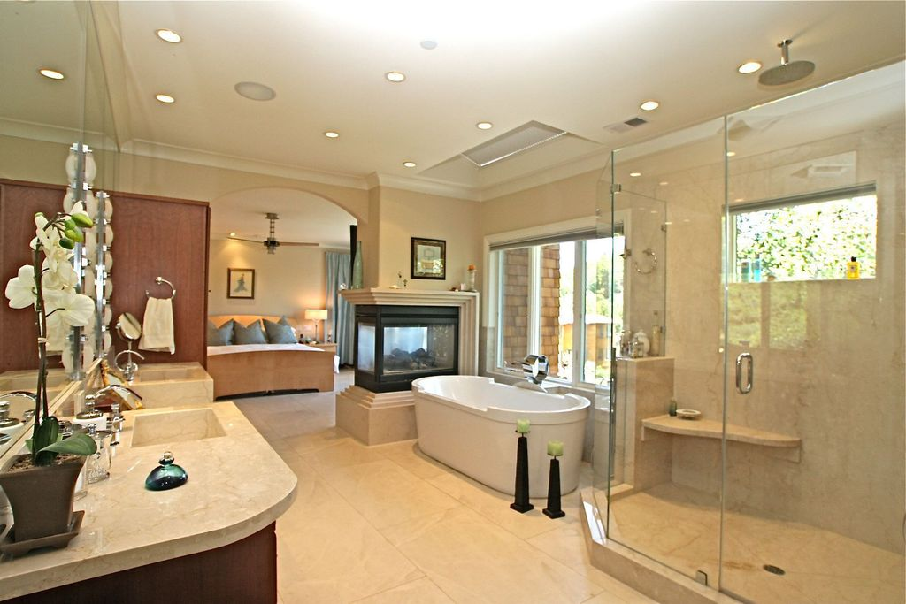 Contemporary Master Bathroom with Shower head, can lights, Rain shower, Fireplace, Soaking, linen and towel storage cabinet