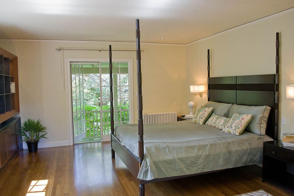 Traditional Guest Bedroom with Crown molding, Balcony, Hardwood floors, French doors