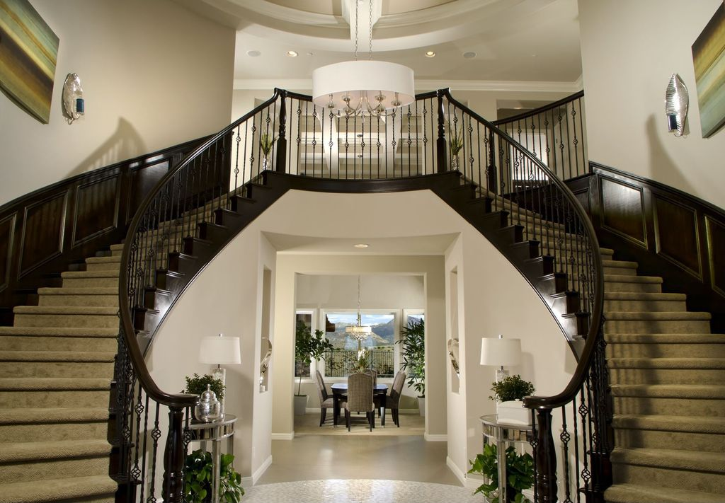 Contemporary Staircase with Hardwood floors, curved staircase, Wainscotting, High ceiling, Chandelier, Double staircase