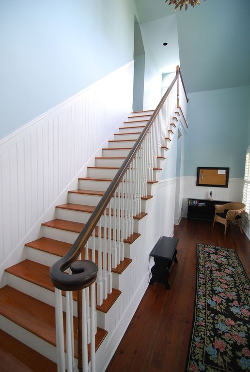 Traditional Staircase with Hardwood floors, High ceiling, Wainscotting, curved staircase