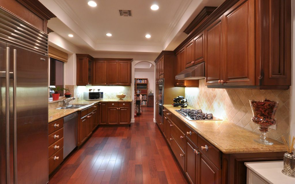 Traditional Kitchen with electric cooktop, Raised panel, Wall Hood, Stone Tile, dishwasher, can lights, Framed Partial Panel