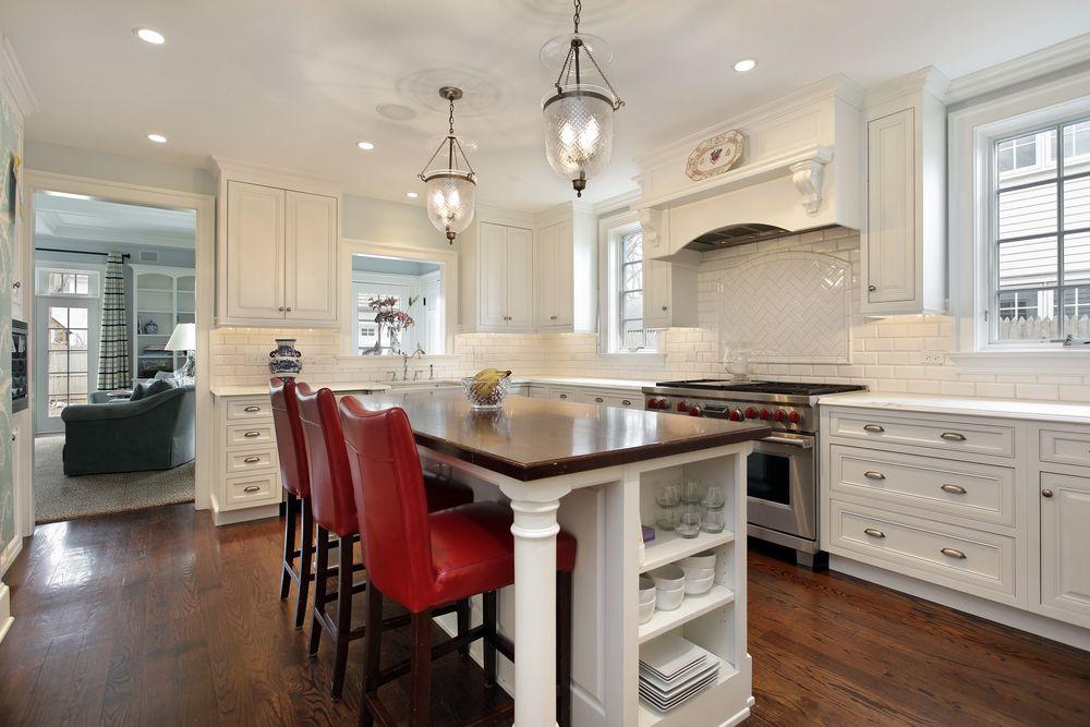 Traditional Kitchen with Standard height, can lights, Pendant light, Hardwood floors, Custom hood, double oven range