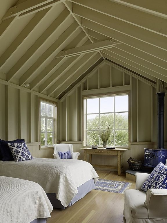Cottage Guest Bedroom with Wainscotting, Vaulted wood ceiling, Exposed beam, Wood Stove fireplace, Wall sconce, Side table
