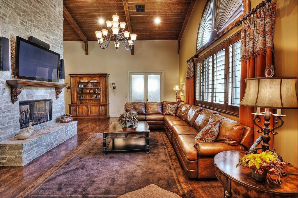 Traditional Living Room with Exposed beam, French doors, Hardwood floors, Arched window, Chandelier, Crown molding