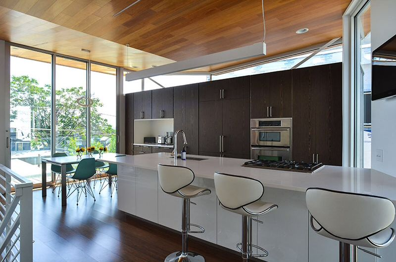 Modern Kitchen with European Cabinets, Breakfast nook, Corian counters, Pendant light, double wall oven, Breakfast bar, Flush