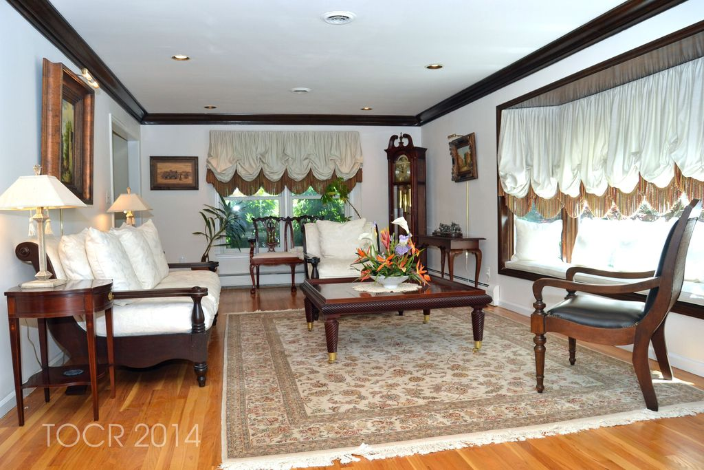 Traditional Living Room with Crown molding, Standard height, can lights, Window seat, Hardwood floors, double-hung window