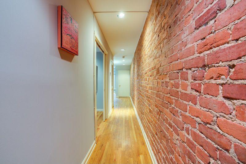 Contemporary Hallway with specialty door, can lights, interior brick, flat door, Hardwood floors, Standard height