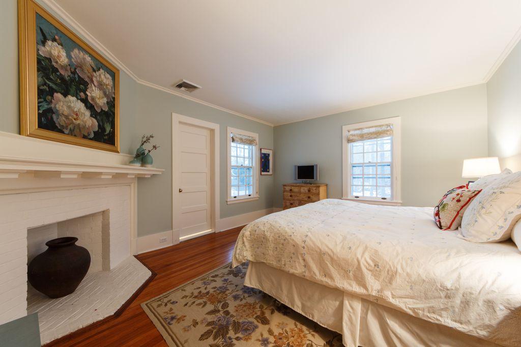 Traditional Guest Bedroom with double-hung window, Crown molding, Fireplace, Standard height, specialty door, Hardwood floors