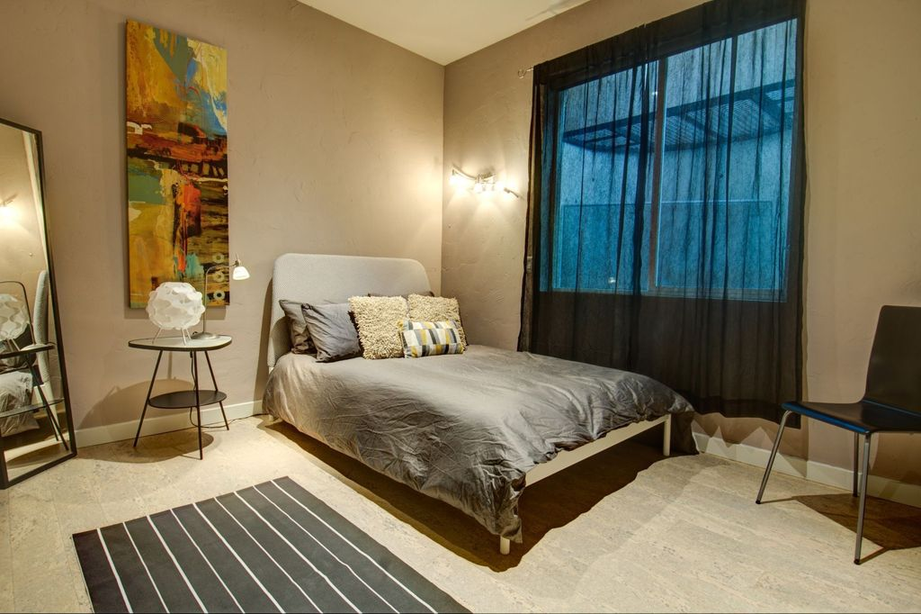 Contemporary Guest Bedroom with Standard height, Hardwood floors, Wall sconce, Casement