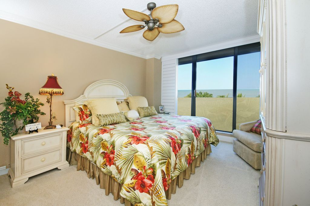 Tropical Master Bedroom with Crown molding, Ceiling fan, French doors, Built-in bookshelf, Carpet, Standard height