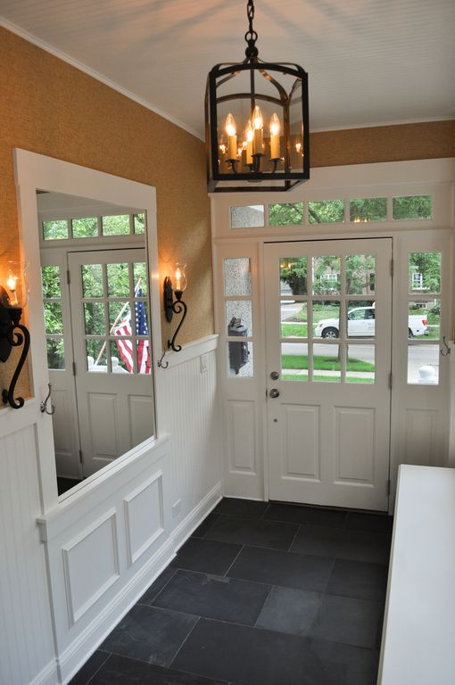 Traditional Entryway with stone tile floors, Crown molding, Chandelier, Transom window, Wainscotting, Wall sconce