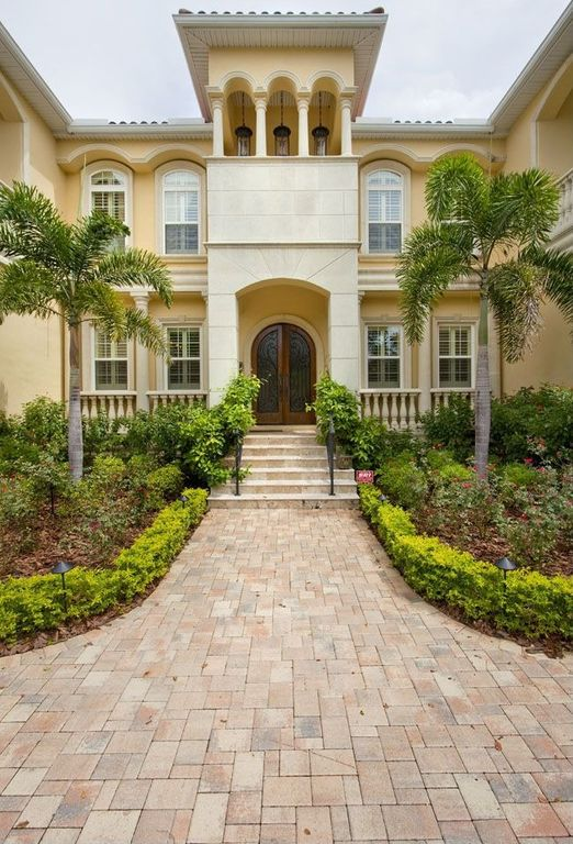 Mediterranean Front Door with double-hung window, exterior brick floors, Arched window, Deck Railing, French doors