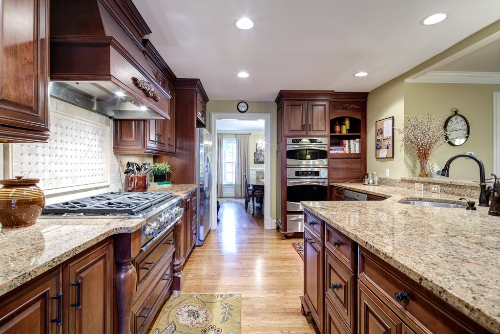Traditional Kitchen with can lights, dishwasher, Complex granite counters, Flat panel cabinets, Stone Tile, Raised panel