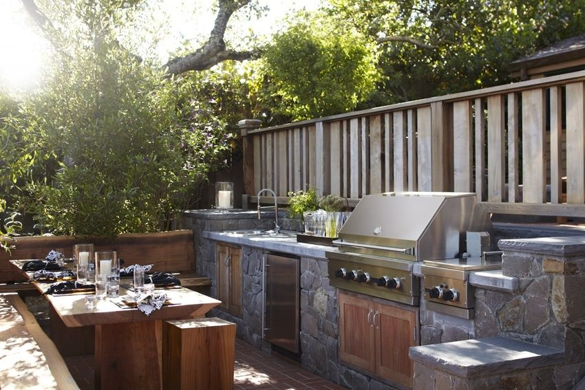 Rustic Patio with Outdoor kitchen, Fence, exterior brick floors
