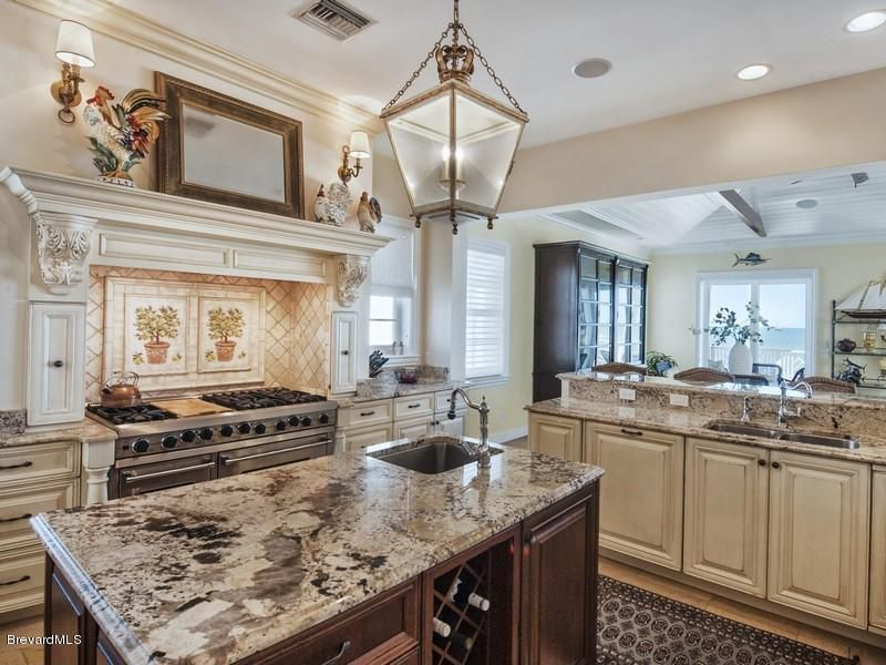 Traditional Kitchen with double-hung window, Wall sconce, Framed Partial Panel, Standard height, Custom hood, Kitchen island