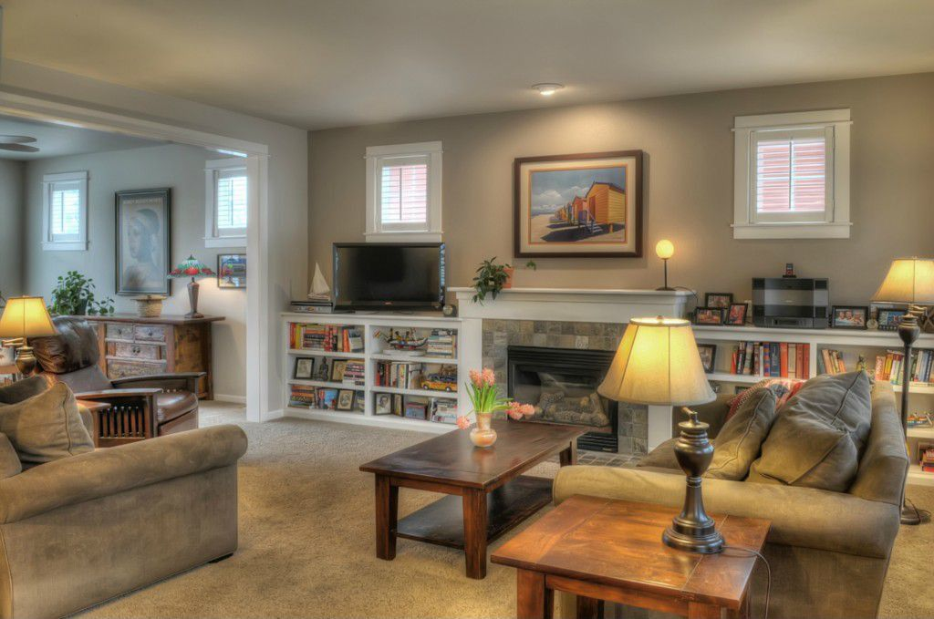 Traditional Living Room with Standard height, Carpet, Built-in bookshelf, Fireplace, stone fireplace, Casement, can lights