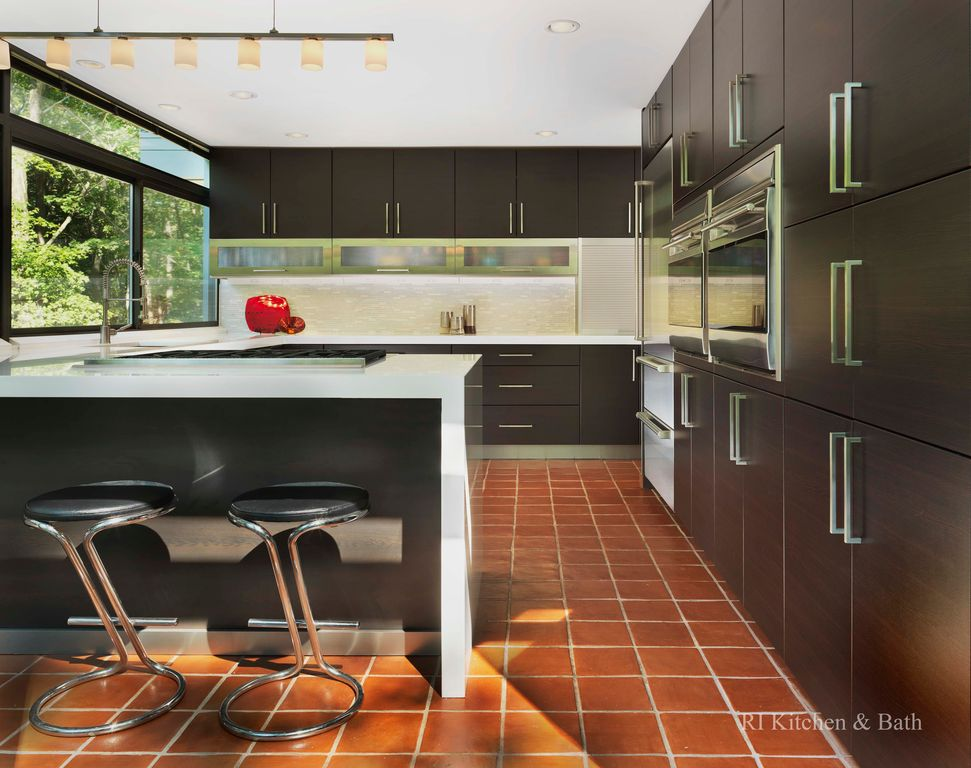 Contemporary Kitchen with terracotta tile floors, Breakfast bar, Standard height, Corian counters, Flush, electric cooktop