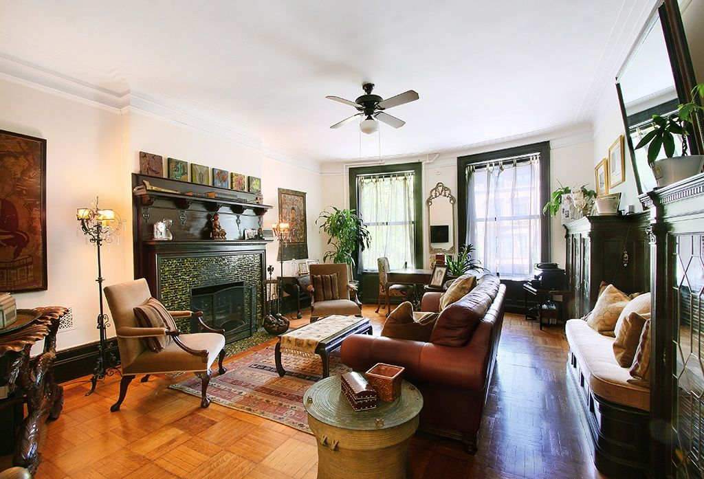 Eclectic Living Room with double-hung window, Built-in bookshelf, Fireplace, Crown molding, Standard height, stone fireplace