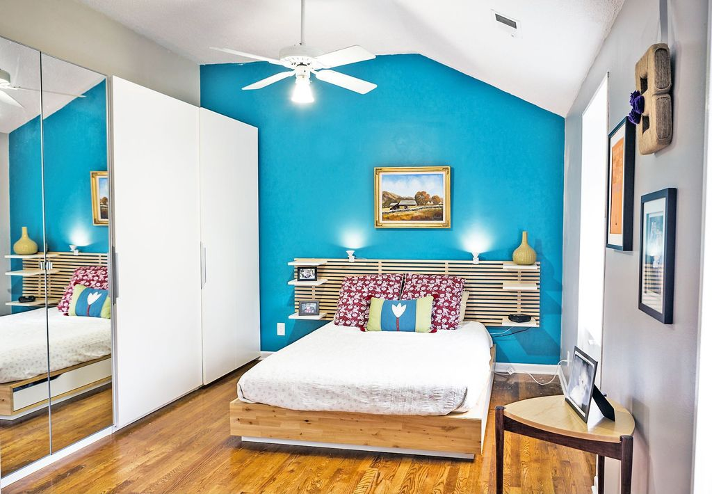 Contemporary Guest Bedroom with Built-in bookshelf, Wall sconce, Hardwood floors, Ceiling fan