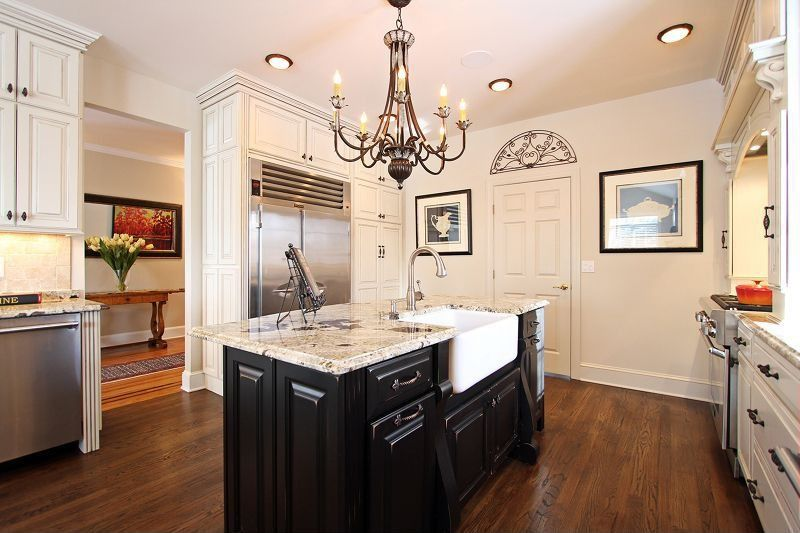 Traditional Kitchen with U-shaped, Chandelier, Custom hood, flush light, Black lacquer cabinets, Oak flooring, Limestone Tile