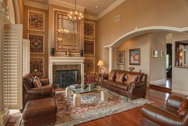 Mediterranean Living Room with metal fireplace, High ceiling, Columns, stone fireplace, Chandelier, can lights, Crown molding