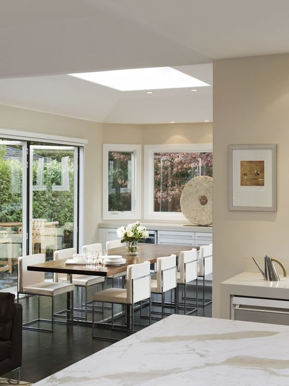 Contemporary Dining Room with Skylight, High ceiling, can lights, folding door, Casement, Hardwood floors