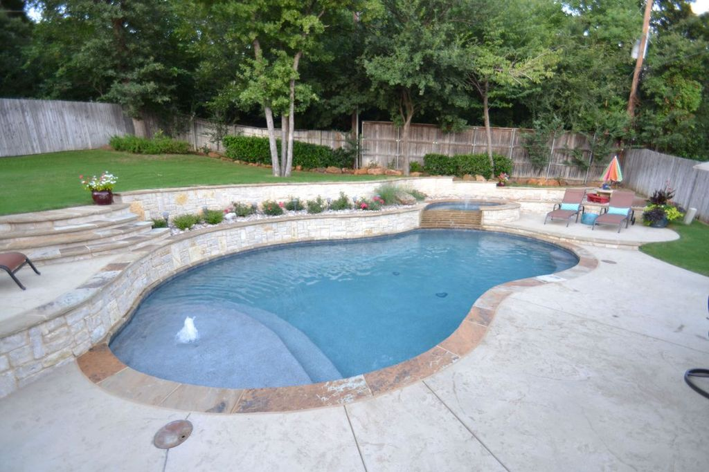 Traditional Swimming Pool with Fence, Outdoor lounge area, Pool with hot tub, exterior stone floors, Pathway, Fountain