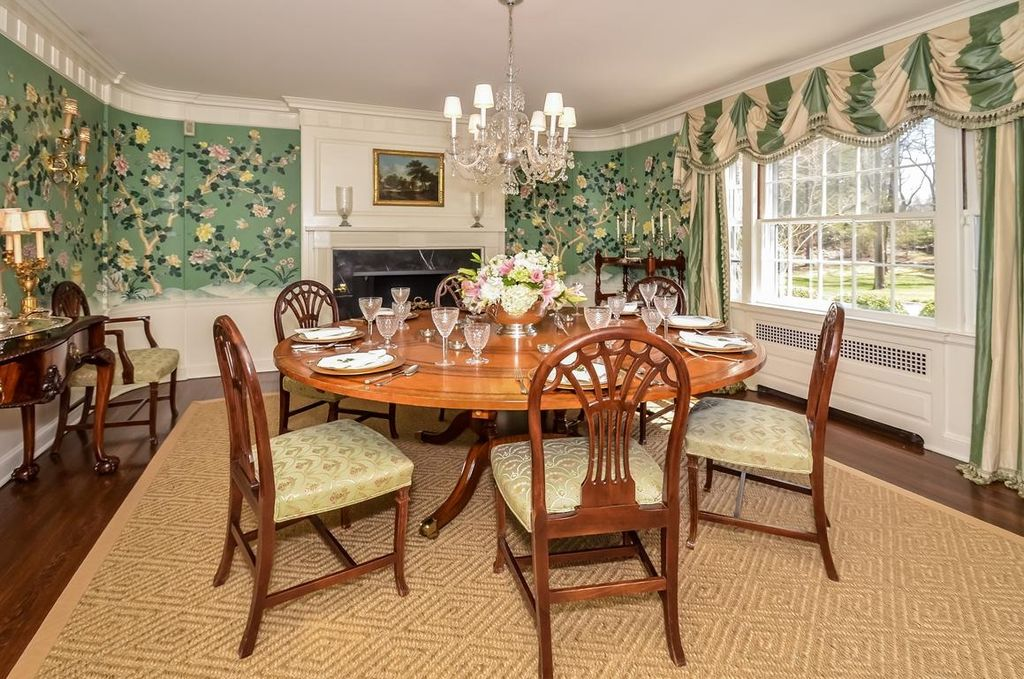 Traditional Dining Room with Chandelier, Standard height, Hardwood floors, insert fireplace, Fireplace, Wall sconce