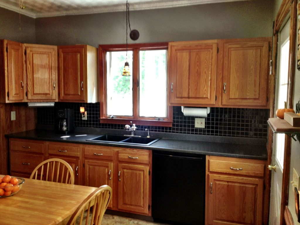 Traditional Kitchen with Casement, Pendant light, Simple granite counters, limestone tile floors, One-wall, dishwasher
