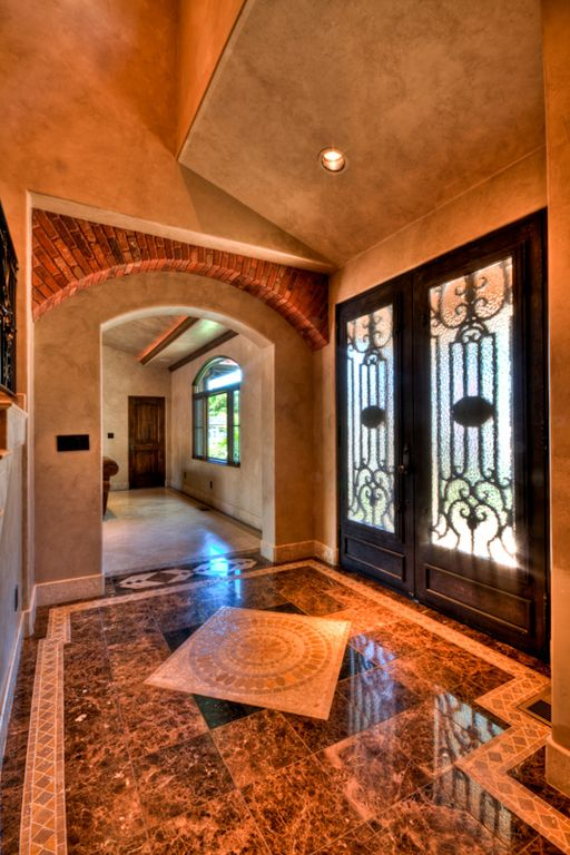Mediterranean Entryway with interior brick, High ceiling, simple marble tile floors, can lights, French doors