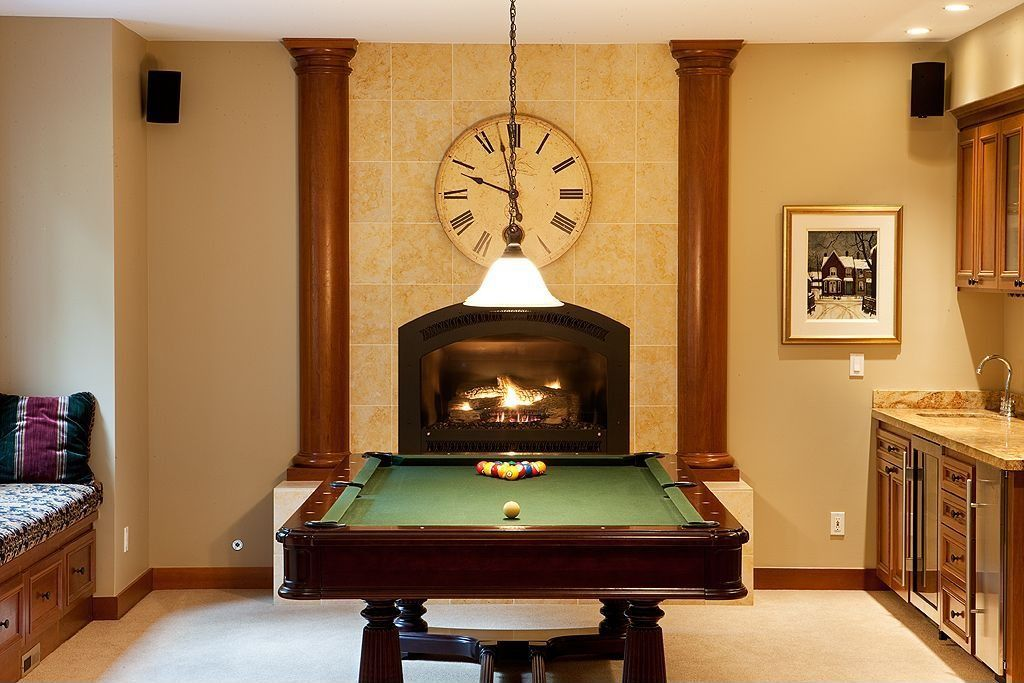 Eclectic Game Room with Cement fireplace, Window seat, Carpet, metal fireplace, Built-in bookshelf, Pendant light