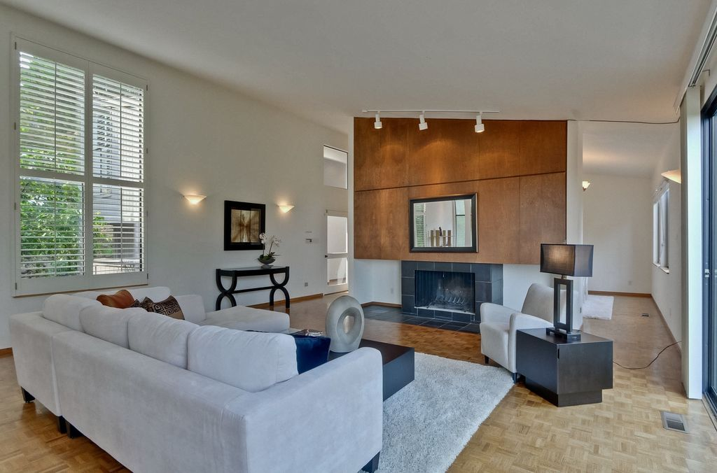 Contemporary Living Room with Wall sconce, flush light, stone fireplace, Hardwood floors
