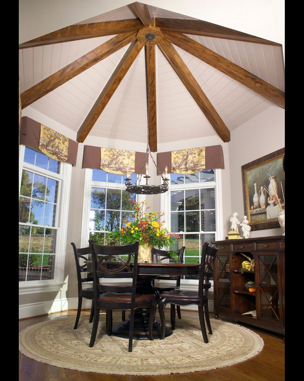 Traditional Dining Room with double-hung window, Chandelier, Hardwood floors, High ceiling, Exposed beam