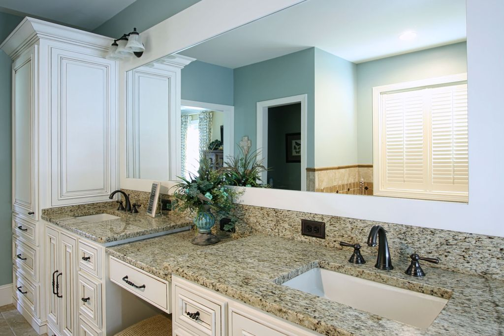 Traditional Master Bathroom with stone tile floors, wall-mounted above mirror bathroom light, Double sink, Casement
