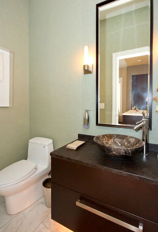 Modern Powder Room with Complex granite counters, Complex Granite, European Cabinets, Wall sconce, stone tile floors, Flush