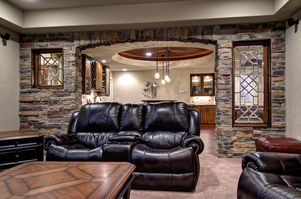 Traditional Basement with Pendant light, Dual leather recliner, Standard height, Casement, Paint, Concrete floors, can lights
