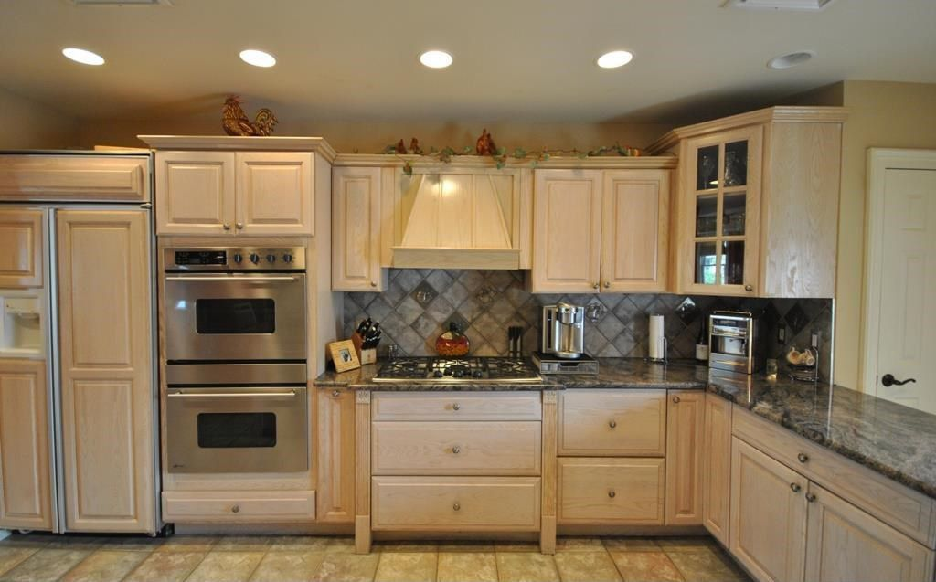 Country Kitchen with Complex granite counters, can lights, Glass panel, Stone Tile, limestone tile floors, Paint 1, L-shaped