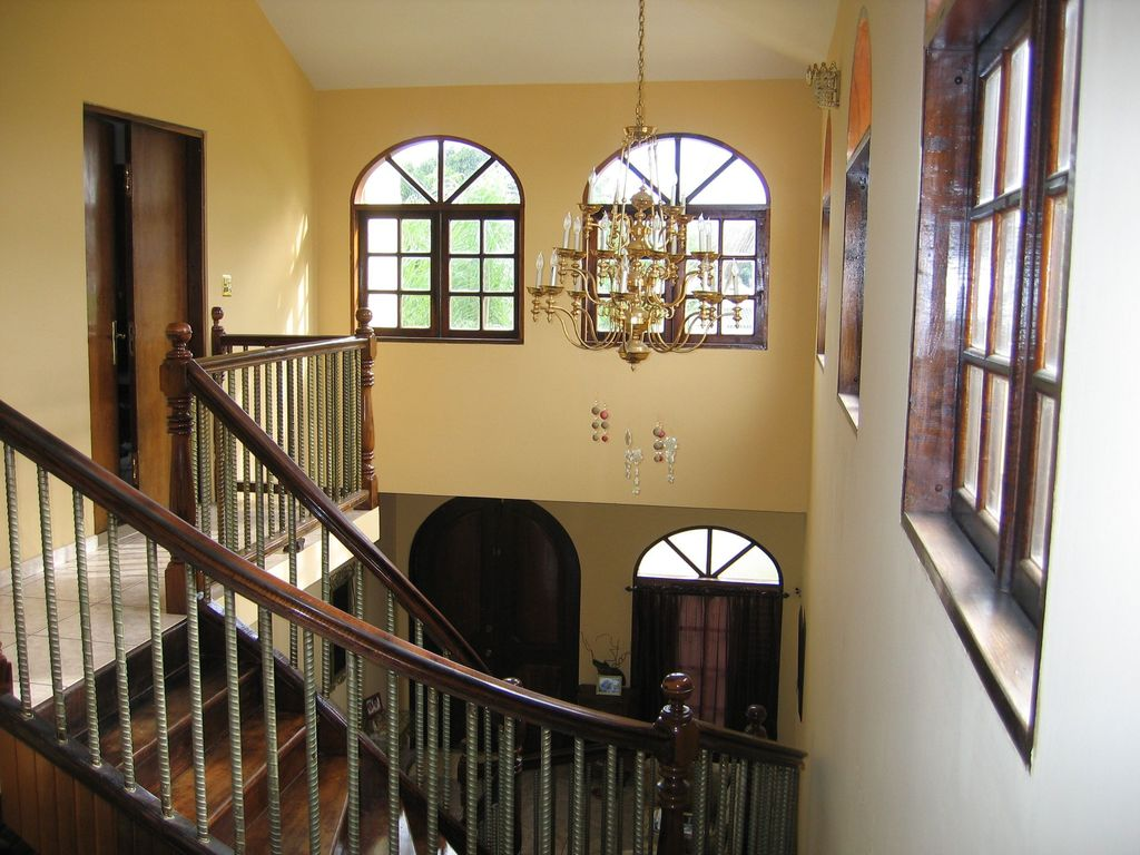 Craftsman Staircase with Hardwood floors, Built-in bookshelf, Arched window, Chandelier, High ceiling, curved staircase